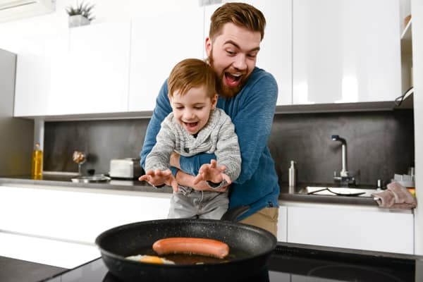 Cheerful bearded father cooking at kitchen with his little son