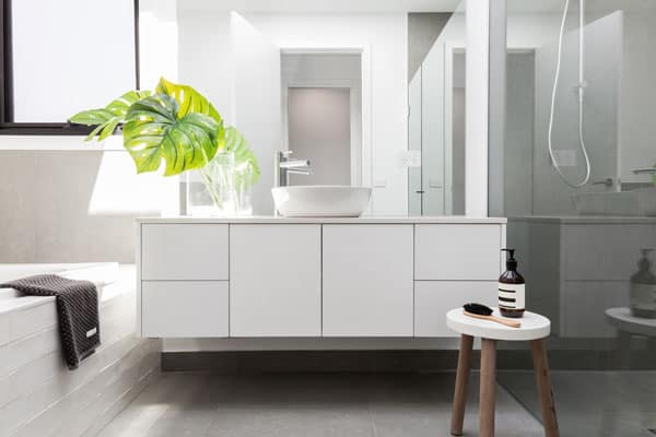 contemporary bathroom with white vanity and tiled bathtub