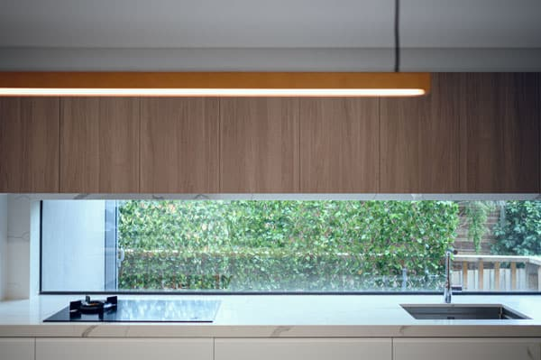 contempory kitchen with clear window splashback and timber doors