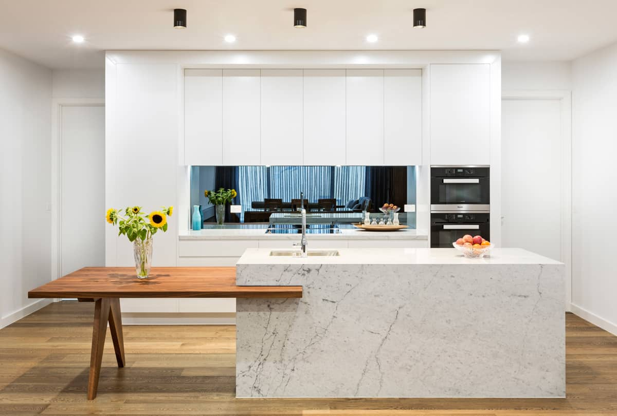 modern-white-kitchen-with-marble-benchtop-and-walnut-timber-table